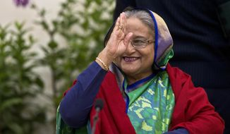 Bangladeshi Prime Minister Sheikh Hasina greets the gathering during an interaction with journalists in Dhaka, Bangladesh, Monday, Dec. 31, 2018. Bangladesh's ruling alliance won virtually every parliamentary seat in the country's general election, according to official results released Monday, giving Hasina a third straight term despite allegations of intimidation and the opposition disputing the outcome. (AP Photo/Anupam Nath)