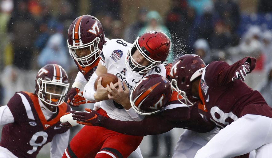 Cincinnati quarterback Hayden Moore, center, is tackled by a group of Virginia Tech defenders as he rushes the ball in the first half of the Military Bowl NCAA college football game, Monday, Dec. 31, 2018, in Annapolis, Md. (AP Photo/Patrick Semansky)