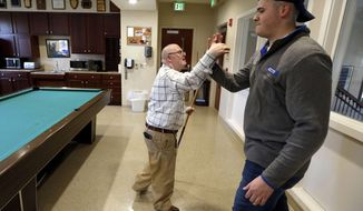 Josh Banks, left, high-fives chapter president Ben Bohannon, right, as Banks shot pool at the University of Kentucky's Farmhouse Fraternity on Rose Lane on Nov. 11, 2018. Farmhouse became the first fraternity at UK to accept a student with Down syndrome when Josh Banks was invited to become a member. Fraternity member Brack Duncan started visiting with Josh Banks through a program, then they became friends. While not a UK student, Josh spends a lot of time at the fraternity and on campus. (Charles Bertram/Lexington Herald-Leader via AP)