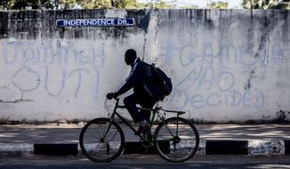 FILE- In this Tuesday, Jan. 24, 2017, file photo, a man rides his bicycle past graffiti on a wall in Banjul, Gambia. Journalists in Gambia have launched a self-regulatory body that they hope will offer legitimacy, and far more freedom, to media emerging from a dictatorship that ruled the tiny West African nation for more than two decades. (AP Photo/Sylvain Cherkaoui, File)