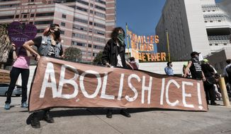 """In this July 2, 2018, file photo, protesters display a sign that reads """"Abolish ICE"""" during a rally in front of the Immigration and Customs Enforcement facility in downtown Los Angeles. (AP Photo/Richard Vogel, File)"""
