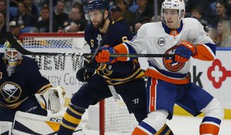 Buffalo Sabres defenseman Marco Scandella (6) and New York Islanders forward Mathew Barzal (13) battle for position during the second period of an NHL hockey game, Monday, Dec. 31, 2018, in Buffalo N.Y. (AP Photo/Jeffrey T. Barnes)