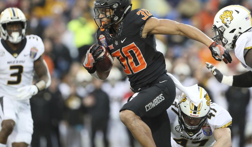 Oklahoma State running back Chuba Hubbard runs breaks away from Missouri linebacker Cale Garrett during the first half of the Liberty Bowl NCAA college football game in Memphis, Tenn., Monday, Dec. 31, 2018. (Joe Rondone/The Commercial Appeal via AP)
