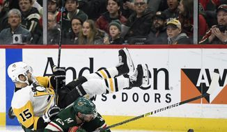 Minnesota Wild's Eric Staal (12) and Pittsburgh Penguins' Riley Sheahan (15) fall while going after the puck during the second period of an NHL hockey game Monday, Dec. 31, 2018, in St. Paul, Minn. (AP Photo/Hannah Foslien)