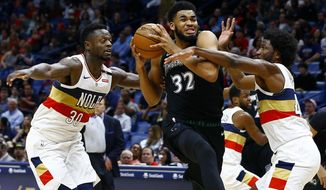 Minnesota Timberwolves center Karl-Anthony Towns (32) drives to the basket as New Orleans Pelicans forwards Julius Randle (30) and Solomon Hill (44) defend during the first half of an NBA basketball game, Monday, Dec. 31, 2018, in New Orleans. (AP Photo/Butch Dill)