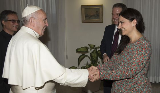 FILE - In this Monday, July 11, 2016 filer, Pope Francis greets Paloma Garcia Ovejero, right, and Greg Burke at the Vatican. The Vatican spokesman, Greg Burke, and his deputy resigned suddenly Monday, Dec. 31, 2018 amid an overhaul of the Vatican's communications operations that coincides with a troubled period in Pope Francis' papacy. In a tweet, Burke said he and his deputy, Paloma Garcia Ovejero, had resigned effective Jan. 1. (L'Osservatore Romano/Pool Photo via AP)