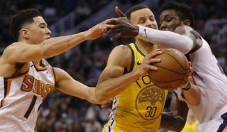 Golden State Warriors guard Stephen Curry (30) drives between Phoenix Suns' Devin Booker (1) and Deandre Ayton during the first half of an NBA basketball game Monday, Dec. 31, 2018, in Phoenix. (AP Photo/Rick Scuteri)