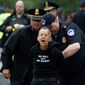 An arrest didn't stop this protester from yelling while blocking traffic on a street between the Supreme Court and the U.S. Capitol. (Associated Press)