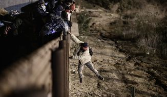 A migrant jumps the border fence to get into the U.S. side to San Diego, Calif., from Tijuana, Mexico, Tuesday, Jan. 1, 2019. Discouraged by the long wait to apply for asylum through official ports of entry, many migrants from recent caravans are choosing to cross the U.S. border wall and hand themselves in to border patrol agents. (AP Photo/Daniel Ochoa de Olza)
