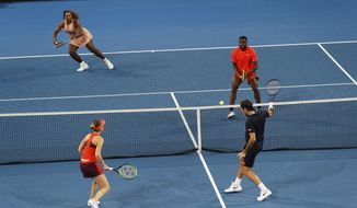 Roger Federer and Belinda Bencic of Switzerland, bottom, in action during their mixed doubles match against Frances Tiafoe and Serena Williams of the United States at the Hopman Cup in Perth, Australia, Tuesday, Jan. 1, 2019. (AP Photo/Trevor Collens)