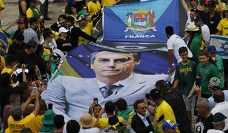 People hold a banner with a photo of Brazil's former army captain Jair Bolsonaro before the swearing-in ceremony, in front of the Planalto palace in Brasilia, Brail, Tuesday Jan. 1, 2019.  Once an outsider mocked by fellow lawmakers for his far-right positions, constant use of expletives and even casual dressing, Bolsonaro is taking office as Brazil's president Tuesday. (AP Photo/Silvia Izquierdo)