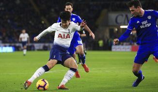 Tottenham Hotspur's Son Heung-min takes a shot to score his side's third goal of the game against Cardiff, during their English Premier League soccer match at Cardiff City Stadium in Cardiff, Wales, Tuesday Jan. 1, 2019. (Mark Kerton/PA via AP)