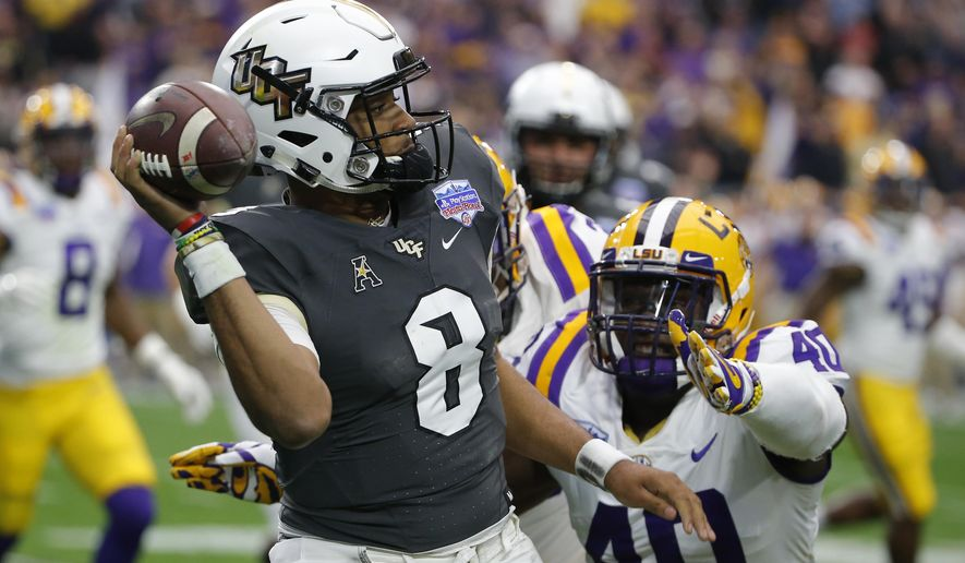 UCF quarterback Darriel Mack Jr. (8) throws the ball away while being pressured by LSU linebacker Devin White (40) in the first half during the Fiesta Bowl NCAA college football game, Tuesday, Jan. 1, 2019, in Glendale, Ariz. (AP Photo/Rick Scuteri)
