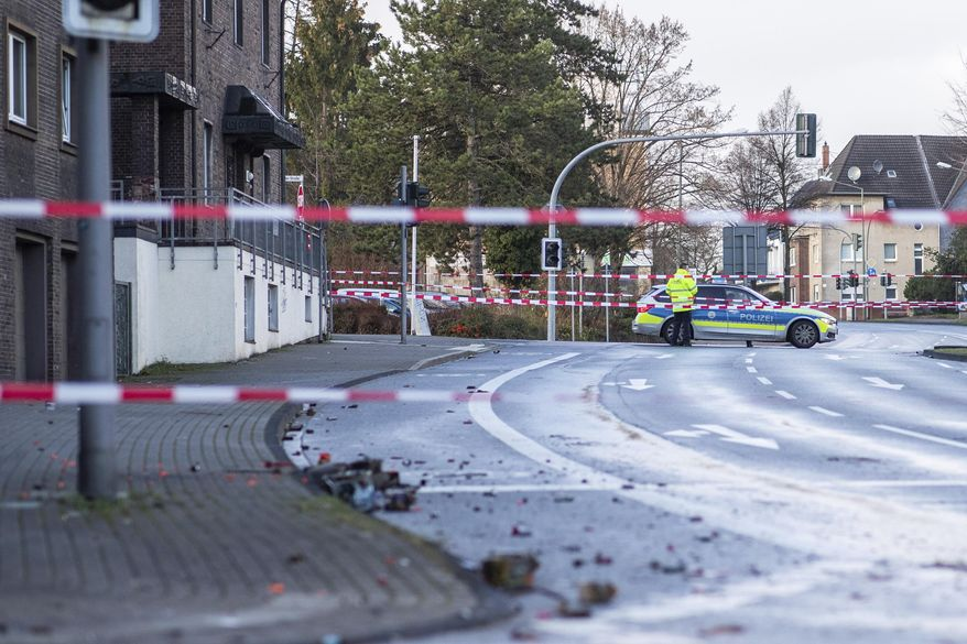 The Police blocks a road in Bottrop, Germany, Tuesday, Jan. 1, 2019. A man has been arrested in Germany after ploughing his car into a crowd of people, injuring at least four, in what appears to have been an intentional attack directed at foreigners, police said Tuesday.  (Marcel Kusch/dpa via AP)