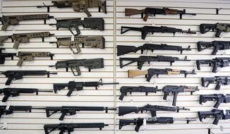 """In this Oct. 2, 2018, semi-automatic rifles fill a wall at a gun shop in Lynnwood, Wash. Starting Tuesday, Jan. 1, 2019, no one under the age of 21 in Washington state will be allowed to purchase a """"semi-automatic assault rifle,"""" under a voter-approved initiative that passed in November. (AP Photo/Elaine Thompson)"""