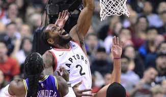 Toronto Raptors forward Kawhi Leonard (2) is fouled going to the net by Utah Jazz forward Jae Crowder (99) as forward Royce O'Neale (23) watches during the first half of an NBA basketball game Tuesday, Jan. 1, 2019, in Toronto. (Frank Gunn/The Canadian Press via AP)