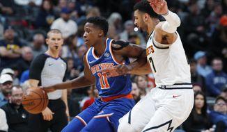 New York Knicks guard Frank Ntilikina, left, drives past Denver Nuggets guard Jamal Murray during the first half of an NBA basketball game Tuesday, Jan. 1, 2019, in Denver. (AP Photo/David Zalubowski)