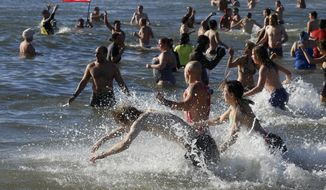 Hundreds of swimmers join in the Coney Island New Year's Day Polar Bear Plunge, Tuesday, Jan. 1, 2019, in the Brooklyn borough of New York. (AP Photo/Mark Lennihan)