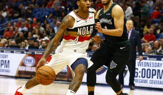 New Orleans Pelicans guard Elfrid Payton (4) drives to the basket around Minnesota Timberwolves guard Tyus Jones (1) during the second half of an NBA basketball game, Monday, Dec. 31, 2018, in New Orleans. (AP Photo/Butch Dill)