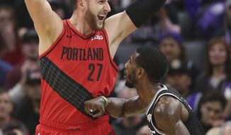 Portland Trail Blazers center Jusuf Nurkic looks to pass the ball over Sacramento Kings guard Iman Shumpert during the first half of an NBA basketball game Tuesday, Jan. 1, 2019, in Sacramento, Calif. (AP Photo/Rich Pedroncelli)
