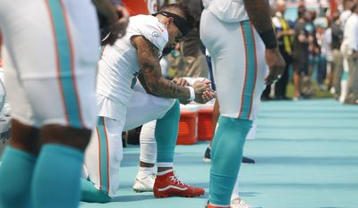 Miami Dolphins wide receiver Kenny Stills and wide receiver Albert Wilson, obscured, take a knee during the singing of the National Anthem before the start of an NFL football game against the Oakland Raiders, Sunday, Sept. 23, 2018 in Miami Gardens, Fla. (AP Photo/Brynn Anderson)