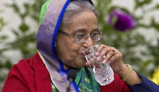 Bangladeshi Prime Minister Sheikh Hasina drinks water during an interaction with journalists in Dhaka, Bangladesh, Monday, Dec. 31, 2018. Bangladesh's ruling alliance won virtually every parliamentary seat in the country's general election, according to official results released Monday, giving Hasina a third straight term despite allegations of intimidation and the opposition disputing the outcome. (AP Photo/Anupam Nath)