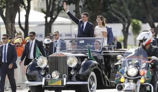 Flanked by first lady Michelle Bolsonaro, Brazil's President Jair Bolsonaro waves as he rides in an open car after his swearing-in ceremony, in Brasilia, Brazil, Tuesday, Jan. 1, 2019. (AP Photo/Andre Penner)