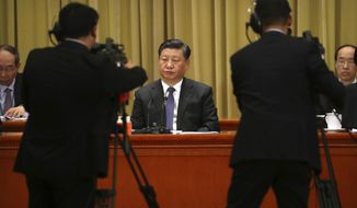 Chinese President Xi Jinping, center, listens to a speech during an event to commemorate the 40th anniversary of the Message to Compatriots in Taiwan at the Great Hall of the People in Beijing, Wednesday, Jan. 2, 2019. Xi urged both sides to reach an early consensus on the unification of China and Taiwan and not leave the issue for future generations. (AP Photo/Mark Schiefelbein, Pool)