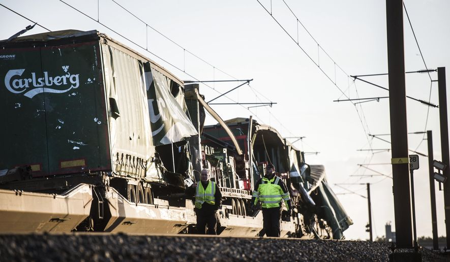 People walk near damaged cargo compartments on a train parked near the Storebaelt bridge, near Nyborg in Denmark, Wednesday, Jan. 2, 2019. Danish police say several people have been killed in a train accident on a bridge linking the central islands of Zealand and Funen. Police did not provide further details about those killed or the number of people injured in Wednesday's incident, which took place about 8 a.m. local time. Danish media reported that a tarpaulin on a freight train hit a passenger train going in the opposite direction, prompting it to brake suddenly. (Tim K. Jensen/Ritzau Scanpix via AP)
