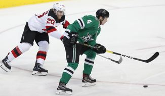 Dallas Stars defenseman Miro Heiskanen (4) and New Jersey Devils center Blake Coleman (20) skate for the puck during the second period of an NHL hockey game in Dallas, Wednesday, Jan. 2, 2019. (AP Photo/LM Otero)