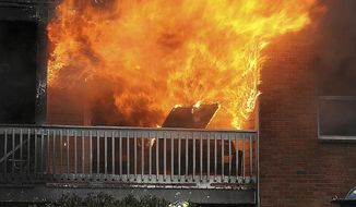 Firefighters try to contain a fire on Wednesday, Jan. 2, 2019 in Fall River, Mass.  A woman crashed her car into the apartment building, setting off the massive fire, (Jack Foley/The Herald News of Fall River via AP)