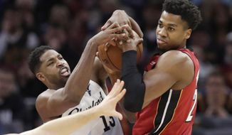 Cleveland Cavaliers' Tristan Thompson, left, and Miami Heat's Hassan Whiteside battle for the ball in the first half of an NBA basketball game, Wednesday, Jan. 2, 2019, in Cleveland. (AP Photo/Tony Dejak)