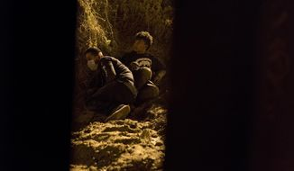 FILE - In this Friday, Nov. 30, 2018, file photo, Salvadoran migrant Cesar Jobet, right, and Daniel Jeremias Cruz, hide from U.S. border agents, after they dug a hole in the sand under the border structure and crossed over to the U.S. side, in Playas de Tijuana, Mexico. The two youths were detected by U.S. border agents and ran back to the Mexican side. Some immigrant youth looking to start over in the United States after fleeing abusive homes are seeing their applications for green cards rejected because the Trump administration says they're too old. A program in place since 1990 has let young immigrants file paperwork before age 21. But the U.S. government says some of these immigrants are too old once they turn 18. (AP Photo/Ramon Espinosa, File)