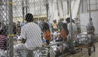 In this June 17, 2018, photo provided by U.S. Customs and Border Protection, people who've been taken into custody related to cases of illegal entry into the United States, sit in one of the cages at a facility in McAllen, Texas. Some immigrant youth looking to start over in the United States after fleeing abusive homes are seeing their applications for green cards rejected because the Trump administration says they're too old. Immigrant advocates have filed lawsuits in New York and California and said hundreds of young people could be affected by the change. (U.S. Customs and Border Protection's Rio Grande Valley Sector via AP)