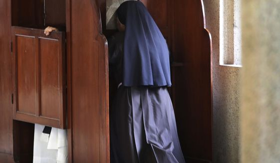In this Sunday, Nov. 4, 2018, photo, a nun partakes in the sacrament of confession at the Immaculate Heart of Mary Cathedral in Kottayam in the southern Indian state of Kerala. An AP investigation has uncovered a decades-long history of nuns in India enduring sexual abuse from within the Catholic church. (AP Photo/Manish Swarup)