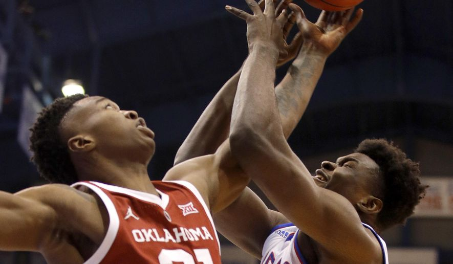 Kansas' Udoka Azubuike, left, and Oklahoma's Kristian Doolittle (21) vie for a rebound during the first half of an NCAA college basketball game Wednesday, Jan. 2, 2019, in Lawrence, Kan. (AP Photo/Charlie Riedel)