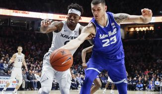 Seton Hall forward Sandro Mamukelashvili (23) and Xavier forward Tyrique Jones (0) chase a rebound during the first half of an NCAA college basketball game Wednesday, Jan. 2, 2019, in Cincinnati. (AP Photo/John Minchillo)