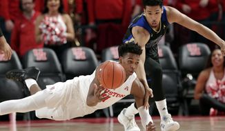 Houston guard Nate Hinton (11) falls as he passes the ball in front of Tulsa guard Zeke Moore (23) after recovering it on a scramble during the first half of an NCAA college basketball game Wednesday, Jan. 2, 2019, in Houston. (AP Photo/Michael Wyke)
