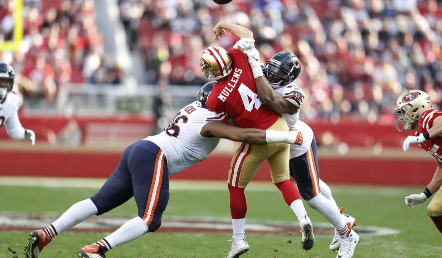 FILE - In this Dec. 23, 2018, file photo, San Francisco 49ers quarterback Nick Mullens (4) is hit by Chicago Bears defensive end Akiem Hicks, left, and outside linebacker Khalil Mack during the second half of an NFL football game in Santa Clara, Calif.  An already strong Bears defense got only better with the acquisition of elite pass rusher Mack before the season. With Mack and Akiem Hicks wreaking havoc up front and Eddie Jackson and Kyle Fuller providing big plays from the secondary, the Bears allowed the fewest points in the NFL this season and appear to have the defense best equipped for a long postseason run starting with Sunday's home game against defending champion Philadelphia. (AP Photo/D. Ross Cameron, File)
