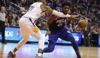 Philadelphia 76ers center Joel Embiid (21) gets fouled by Phoenix Suns forward Richaun Holmes in the second half during an NBA basketball game, Wednesday, Jan. 2, 2019, in Phoenix. The 76ers defeated the Suns 132-127. (AP Photo/Rick Scuteri)