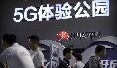 Visitors look at a display for 5G wireless technology from Chinese technology firm Huawei at the PT Expo in Beijing, Wednesday, Sept. 26, 2018. The government-organized event comes amid a mounting tariff war with Washington over Beijing's plans for the state-led creation of its own global technology competitors. (AP Photo/Mark Schiefelbein)