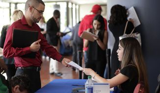 FILE- In this Jan. 30, 2018, file photo, an employee of Aldi, right, takes an application from a job applicant at a JobNewsUSA job fair in Miami Lakes, Fla. On Thursday, Jan. 3, 2019, payroll processor ADP reports how many jobs private employers added in December. (AP Photo/Lynne Sladky, File)