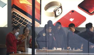 Customers visit an Apple store in Beijing, China, Thursday, Jan. 3, 2019. Apple Inc.'s $1,000 iPhone is a tough sell to Chinese consumers who are jittery over an economic slump and a trade war with Washington. The tech giant became the latest global company to collide with Chinese consumer anxiety when CEO Tim Cook said iPhone demand is waning, due mostly to China. Weak consumer demand in the world's second-largest economy is a blow to industries from autos to designer clothing that are counting on China to drive revenue growth. (AP Photo/Ng Han Guan)