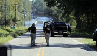 FILE - In this Wednesday, Sept. 19, 2018, file photo, responders congregate near where two people drowned the evening before when they were trapped in a Horry County Sheriff's transport van while crossing an overtopped bridge over the Little Pee Dee River on Highway 76, during rising floodwaters in the aftermath of Hurricane Florence in Marion County, S.C. Charges are expected to be filed Friday, Jan. 4, 2019, against two South Carolina law enforcement officers who were transporting two mental patients who drowned while locked in the back of a van during the hurricane. (AP Photo/Gerald Herbert, File)