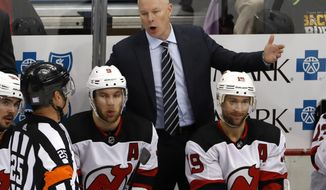 FILE - In this Nov. 5, 2018, file photo, New Jersey Devils head coach John Hynes talks with referee Marc Joannette (25) during the third period of an NHL hockey game against the Pittsburgh Penguins, in Pittsburgh. The New Jersey Devils have given coach John Hynes a multiyear contract extension. The team announced the deal Thursday, Jan. 3, 2019, saying Hynes' leadership has been instrumental in building a culture and systems for the development of the players. (AP Photo/Gene J. Puskar, File)