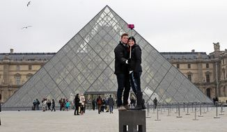 FILE - In this Tuesday, Jan. 6, 2015, Chris Baker and Jennifer Hinson from Nashville, Tennessee, use a selfie stick in front of the Louvre Pyramide in Paris. The world's most visited museum, the Louvre in Paris registered 10.2 million visitors in 2018, a record boosted by a rise of foreign tourists and pop star Beyonce's video paying tribute to the Mona Lisa and others world-famous artworks. (AP Photo/Remy de la Mauviniere, File)