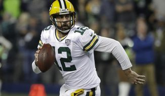 FILE - In this Nov. 15, 2018, file photo, Green Bay Packers quarterback Aaron Rodgers looks to pass against the Seattle Seahawks during the first half of an NFL football game, in Seattle. The Packers play the Minnesota Vikings on Sunday. The NFL's six highest-paid quarterbacks in 2018 will be spectators this postseason. Green Bay's Aaron Rodgers ($33.5 million), Atlanta's Matt Ryan ($30 million), Minnesota's Kirk Cousins ($28 million), San Francisco's Jimmy Garoppolo ($27.5 million), Detroit's Matthew Stafford ($27 million) and Oakland's Derek Carr ($25 million) couldn't lead their teams to the playoffs. (AP Photo/Elaine Thompson) ** FILE **