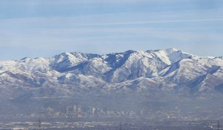 In this Dec. 14, 2018, photo, an inversion settles over Salt Lake City. Inversions hover over Salt Lake City as cold, stagnant air settles in the bowl-shaped mountain basins, trapping tailpipe and other emissions that have no way of escaping to create a brown, murky haze the engulfs the metro area. Doctors warn that breathing the polluted air can cause lung problems and other health concerns, especially for pregnant women and people with respiratory issues. (AP Photo/Rick Bowmer)