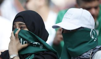 """FILE - In this Thursday, June 14, 2018 filer, Saudi women sit in the stands ahead of the group A match between Russia and Saudi Arabia which opens the 2018 soccer World Cup at the Luzhniki stadium in Moscow, Russia. Facing increasing criticism by government members over the decision to play the Italian Super Cup in Saudi Arabia, Serie A's president is hailing the match as a """"historic"""" opportunity for Saudi women to attend an international game. After tickets for the Jan. 16 match went on sale with specified sectors for """"singles"""" and """"families"""" to separate men and women, Interior Minister Matteo Salvini declared that it was """"a shame."""" There had already been calls for the game to be moved after the killing of Washington Post columnist Jamal Khashoggi. (AP Photo/Hassan Ammar, File )"""