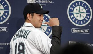 Seattle Mariners pitcher Yusei Kikuchi smiles and shows off his new jersey following a news conference after his signing with the team, Thursday, Jan. 3, 2019, in Seattle. Kikuchi is the latest Japanese star to decide on calling Seattle home in the majors. The Mariners hope their new left-handed pitcher can help in their rebuild process. (AP Photo/Elaine Thompson)